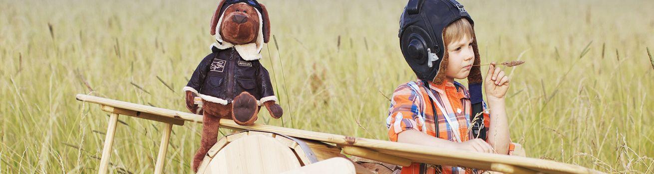 Снимка на момче с плюшена играчка куче.